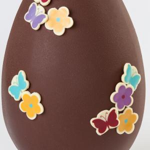 Huevo de chocolate de Pascua decorado con flores y mariposas