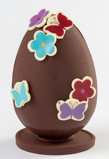 Huevo mediano de chocolate negro decorado con flores y mariposas coloridas para Pascua